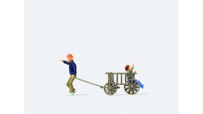 homme tirant une charette avec un enfant